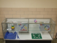 A display case exhibiting models demonstrating Lego math.